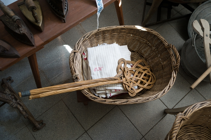 antique rug beaters in a laundry basket