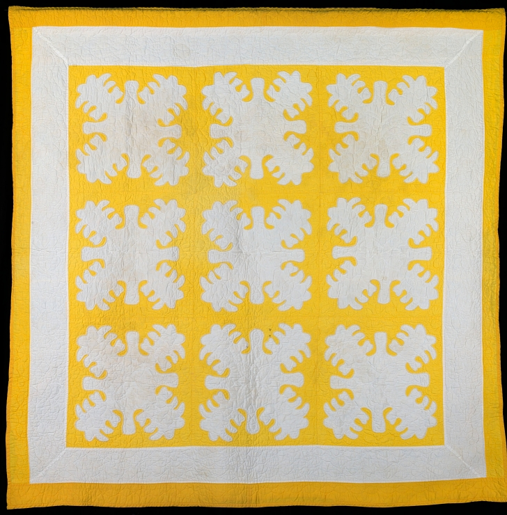 yellow and white Hawaiian quilt depicting breadfruit plants