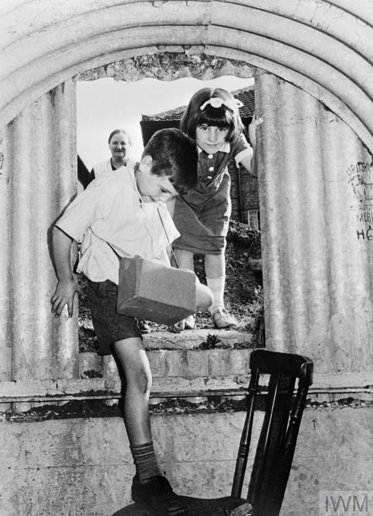 children entering a London Anderson bomb shleter in 1940