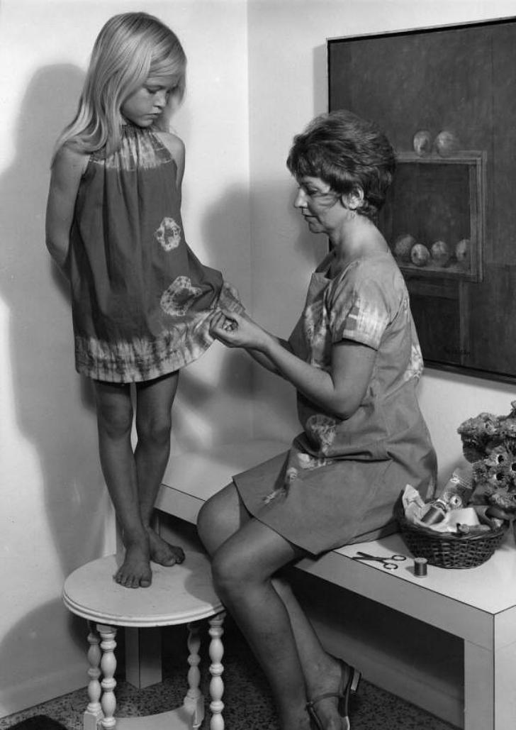 woman inspecting dye pattern on dress worn by child