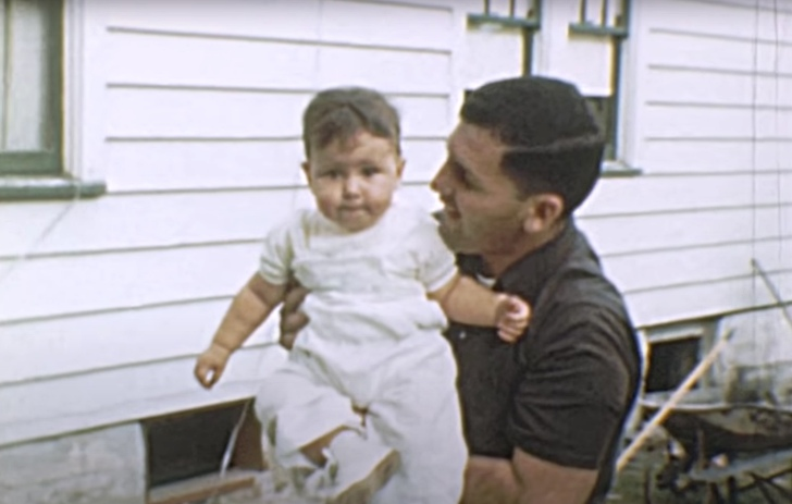 father holding up his toddler son, 1950s