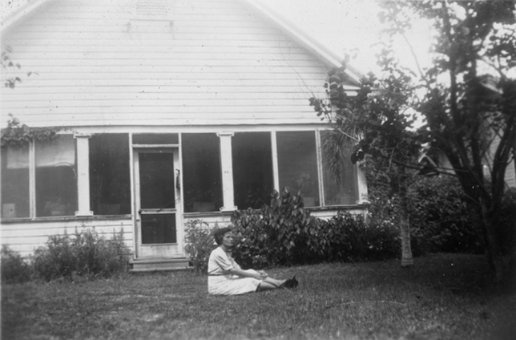 woman sitting on the ground in front of a house, 1940s