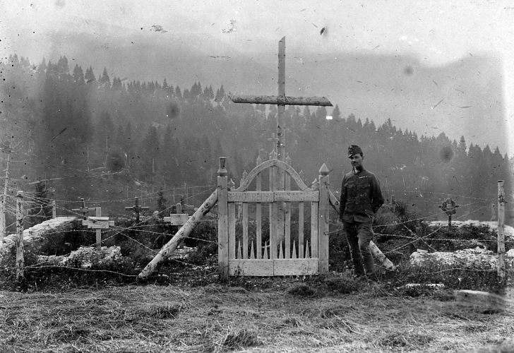 soldier standing in front an Alpine graveyard of those who died in the White War, 1917