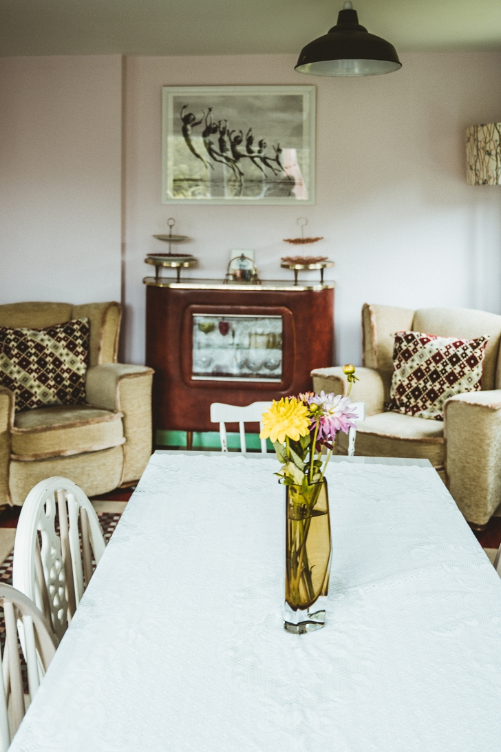 living and dining room filled with a mix of vintage furniture styles