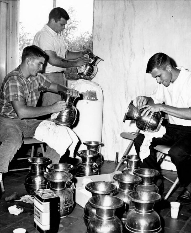 young men cleaning spittoons
