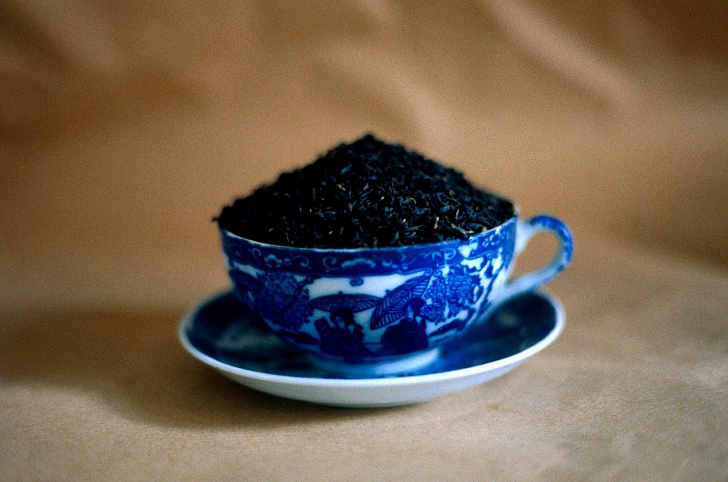 blue willow teacup filled to brimming with loose tea