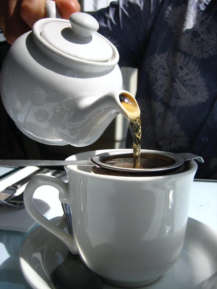 tea being poured into a teacup from a teapot