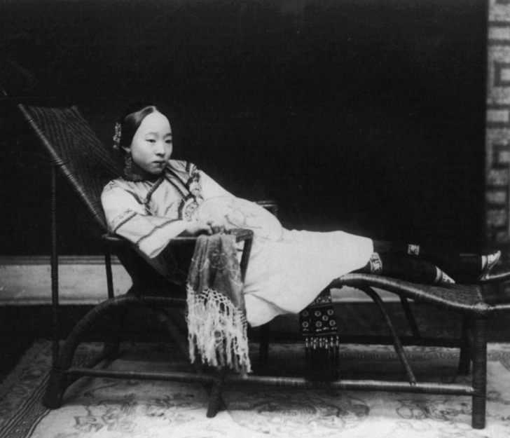 woman with bound feet on chaise longue chair