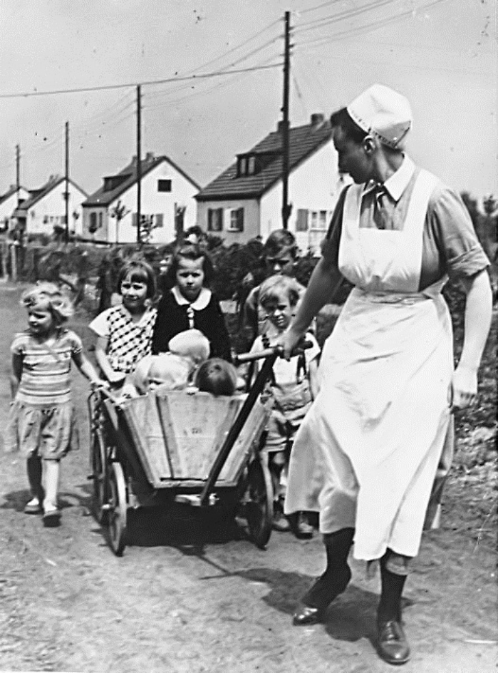 an NSV nurse pulling a cart of children during WWII