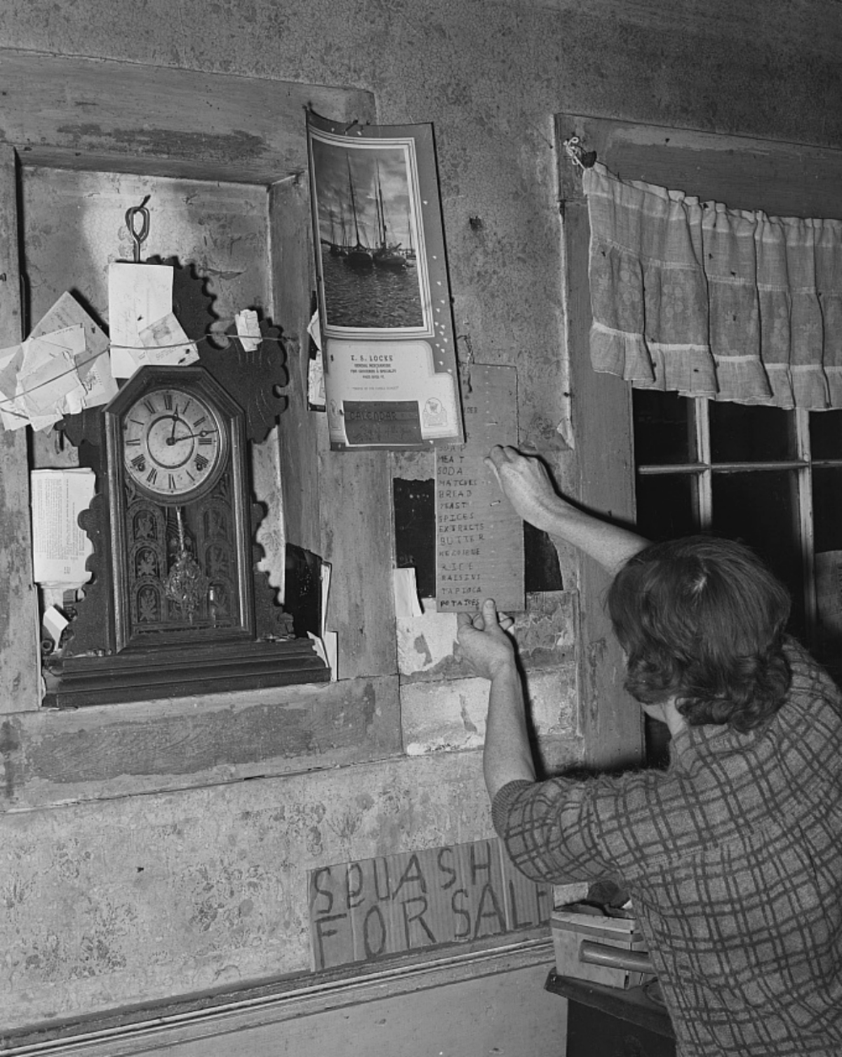 woman tacking a grocery list to the wall, 1930s