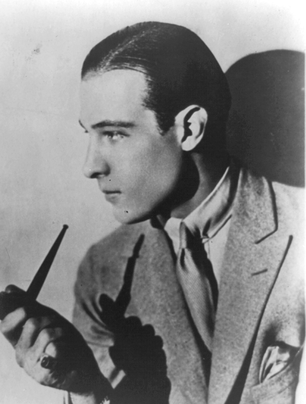 Rudolph Valentino holding a pipe