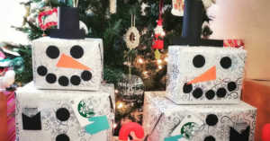 two snowman gift towers with gift cards in front of a Christmas tree