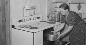 1940s housewife pulling a covered pan out of the oven