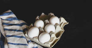 half carton of eggs next to a blue and white dish towel